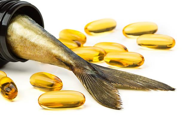 Fish oil capsules and fish tail in brown jar stock photo