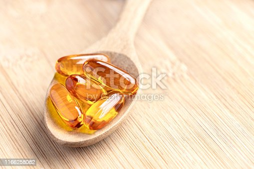 istock Fish oil capsules as a dietary supplement containing omega-3 and vitamin a is high for health care. Salmon oil into spoon on the wood table. 1166258082