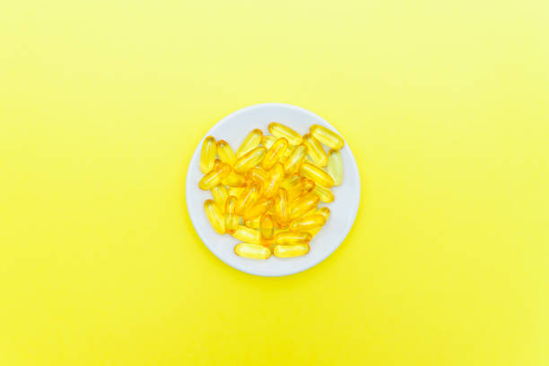 fish oil capsules in a white plate on yellow background. top view, flat lay, copy space. - vitamin d zdjęcia i obrazy z banku zdjęć