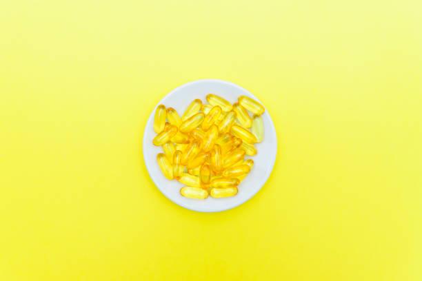 sarı arka planda beyaz bir tabakta balık yağı kapsülleri. üst görünüm, düz döşeme, kopyalama alanı. - vitamin d stok fotoğraflar ve resimler
