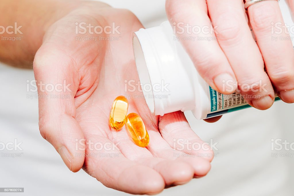 Fish oil capsules in hand stock photo