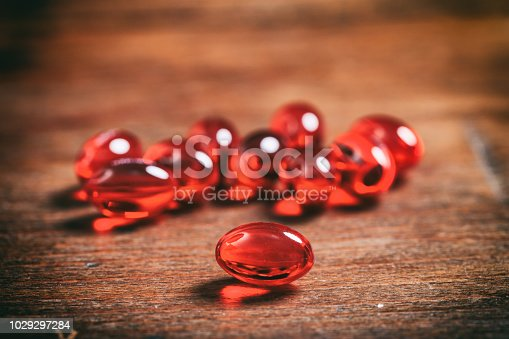 Fish oil capsules on a wooden background