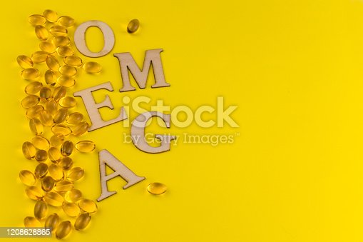 istock fish oil capsules on a yellow background. Copy space. 1208628865