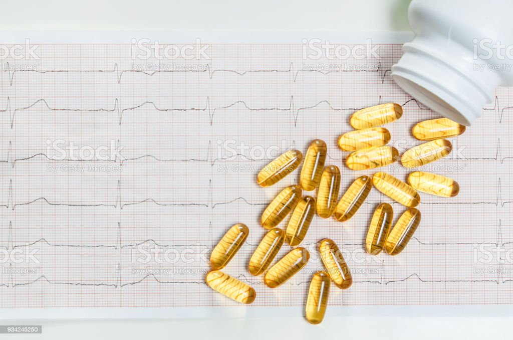 Fish oil capsules on cardiogram ECG, healthy heart concept stock photo