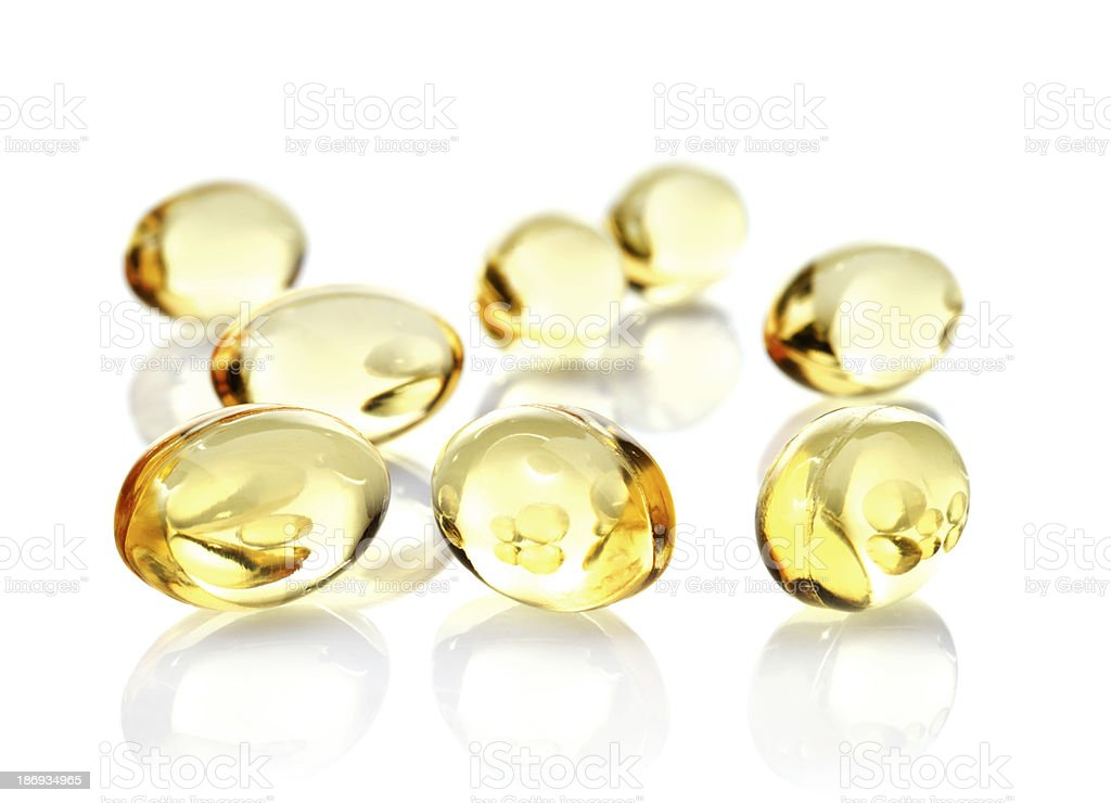 Fish oil capsules scattered over a reflective white surface royalty-free stock photo