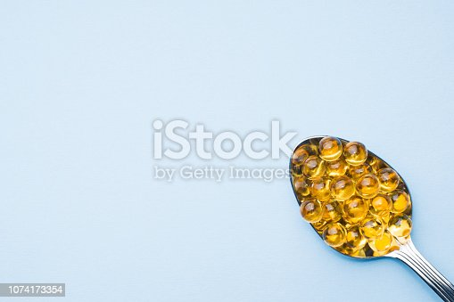 istock Fish oil capsules with omega 3 and vitamin D blue texture, healthy diet concept, selective focus. 1074173354