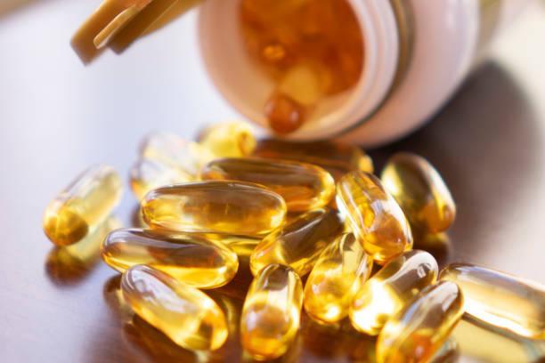 капсулы рыбьего жира с омега-3 и витамином d в стеклянной бутылке на деревянной текстуре, концепция здорового питания, крупным планом выстре - vitamin d стоковые фото и изображения