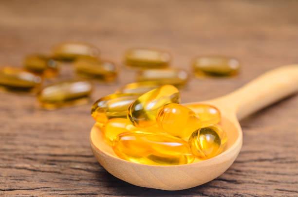 aceite de pescado en cuchara de madera - omega 3 fotografías e imágenes de stock