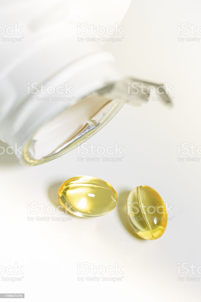 fish oil pill fall from white container royalty-free stock photo