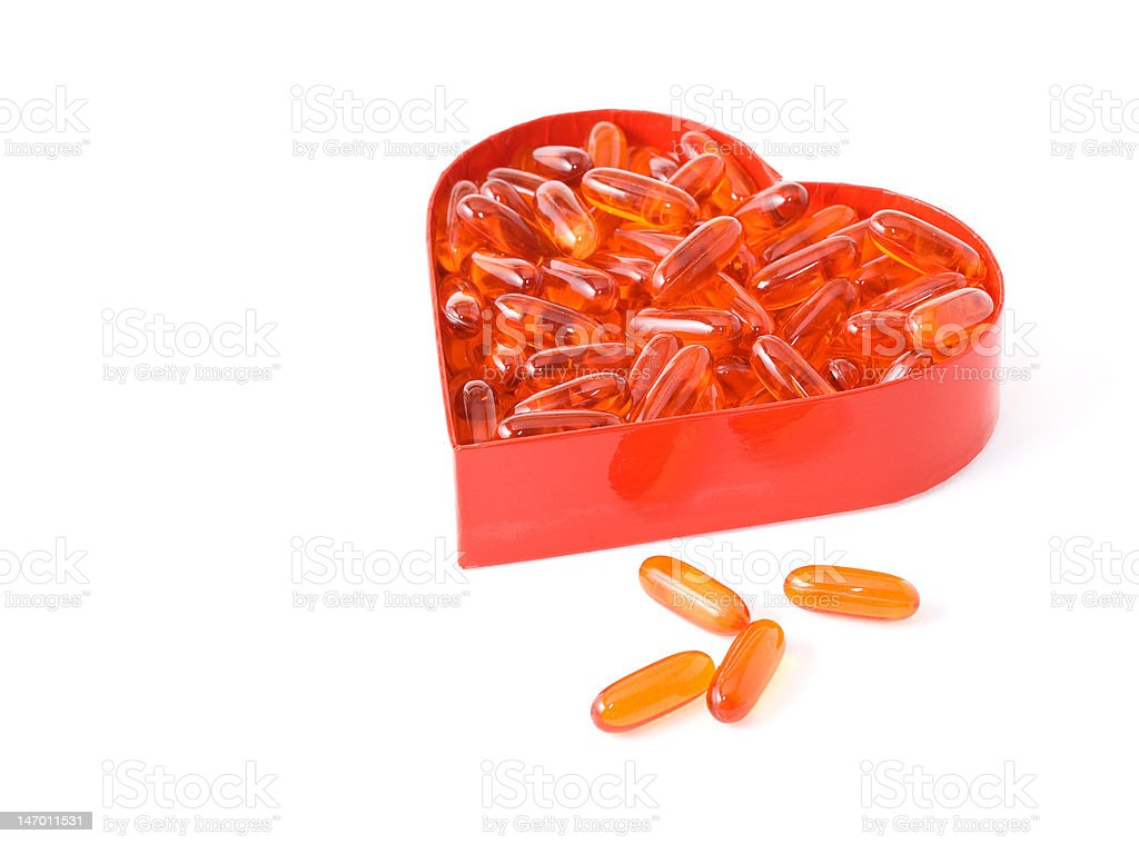 Fish oil pills in red heart shaped box royalty-free stock photo