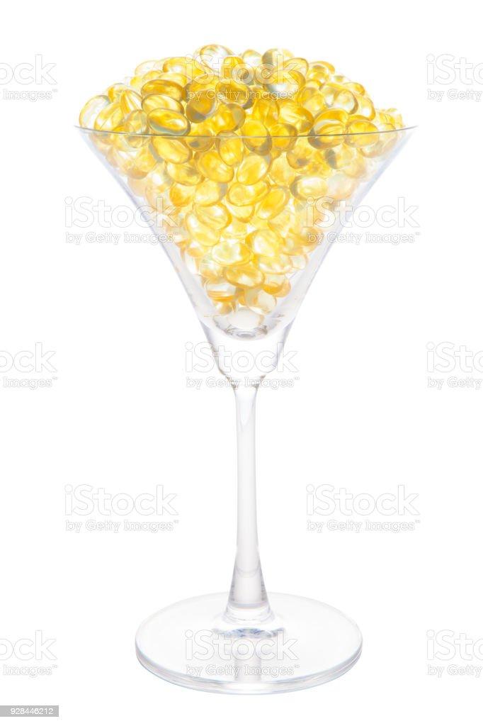 Óleo de peixe cápsula macia em copo de coquetel com traçado de recorte isolado no fundo branco. - foto de acervo