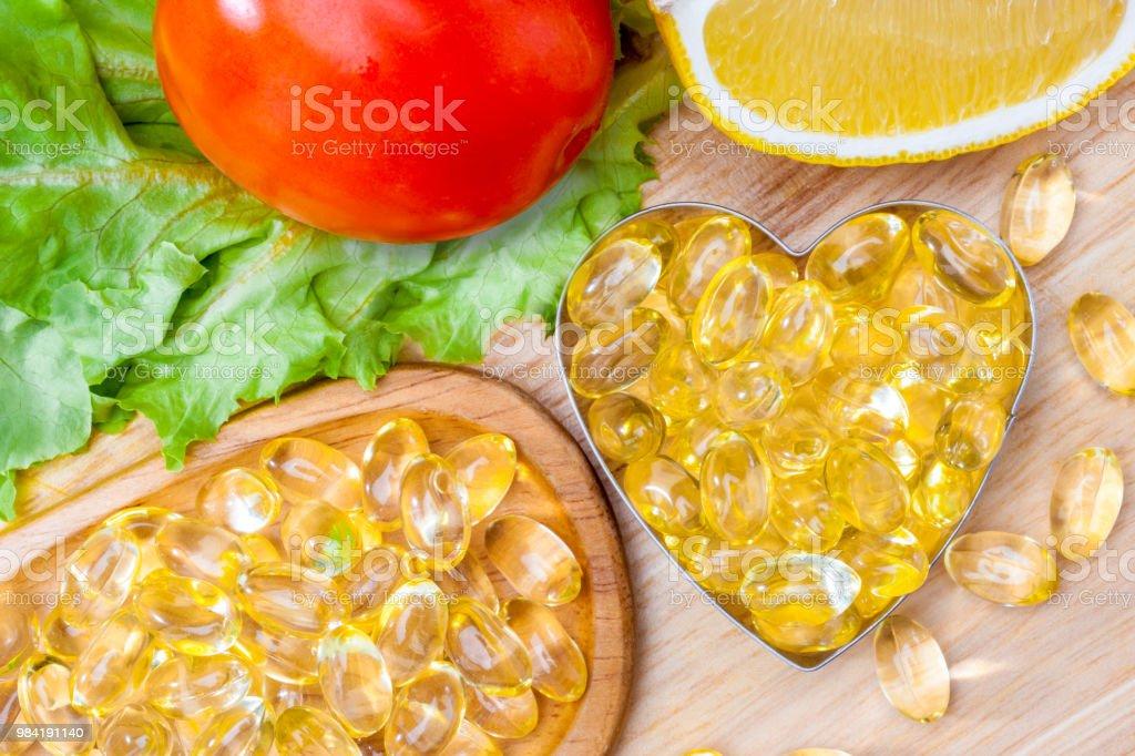 Vis Olie Zachte Capsule Omega 3 Aanvulling Op Voedsel Vitamine D Capsules In Hartvormige Met Groenten En Fruit Groenen Tomaat Citroen Op Hout Stilleven Van Gezonde Voeding En Aanvullende Voeding Concept Stockfoto