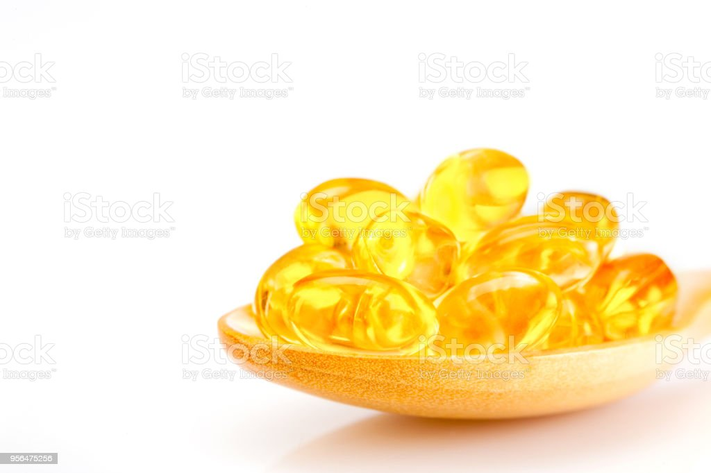 Fish oil, soft capsule, omega, supplement in wooden spoon isolated  on white background ,healthy product concept close up stock photo