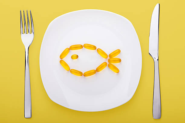 fish oil soft gels lying on a plate - cod liver oil stock photos and pictures