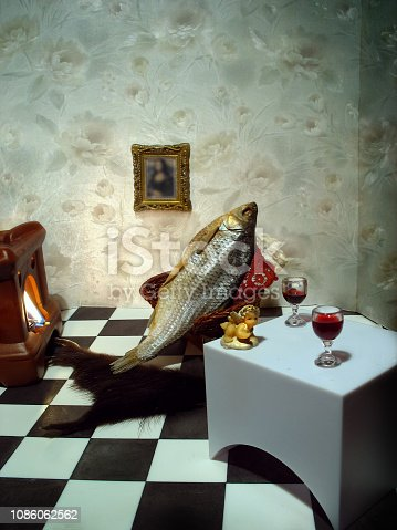 fish resting in the armchair by the fireplace with a glass of wine