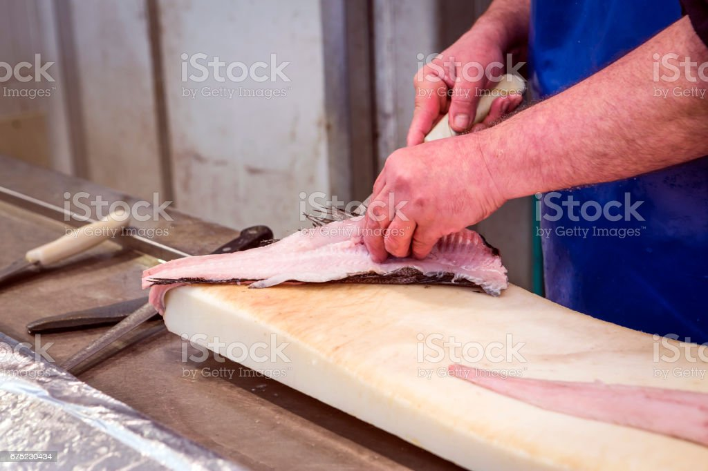 Fish seller short with a thin knife on the market royalty-free stock photo