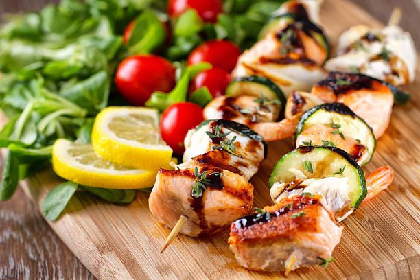 Spieße mit Fisch, Salat – Foto
