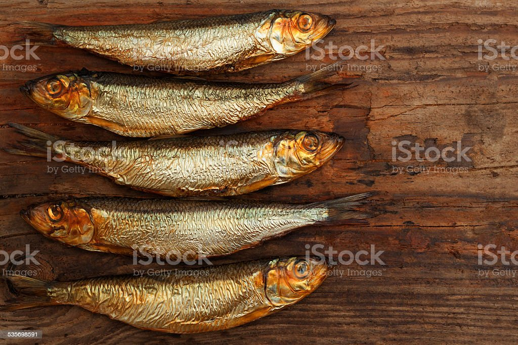 fish smoked herring sprat wood old board stock photo
