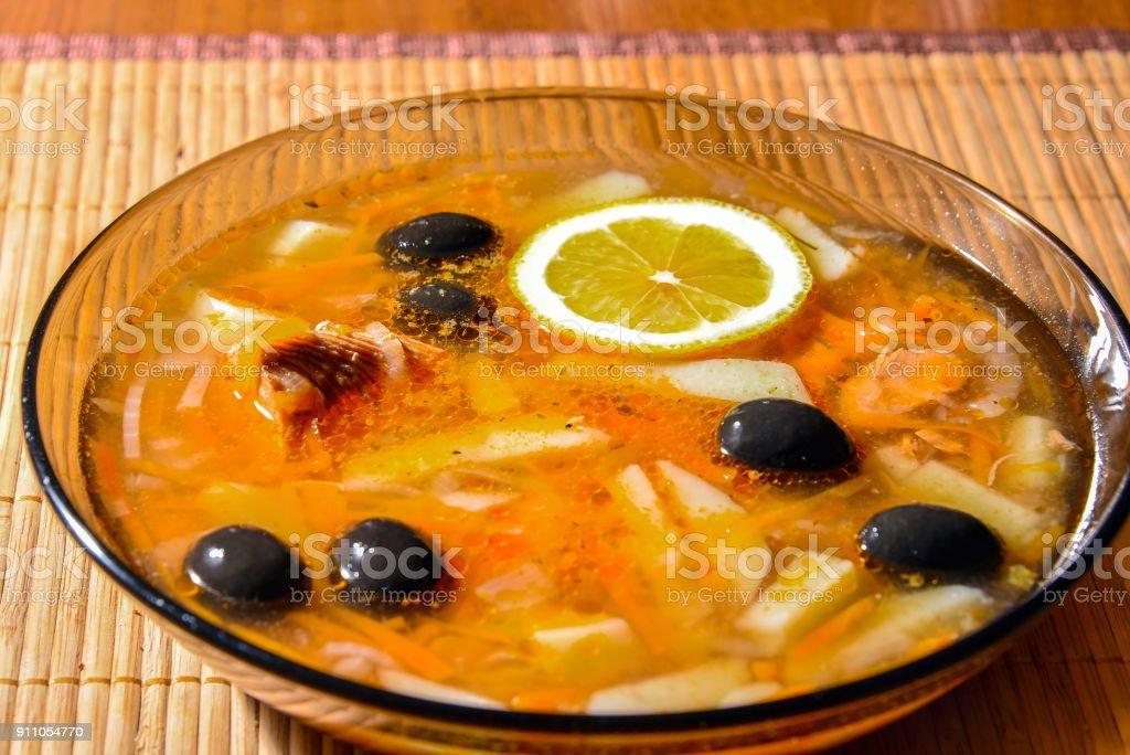 Fish Solyanka in a plate on a bamboo napkin stock photo