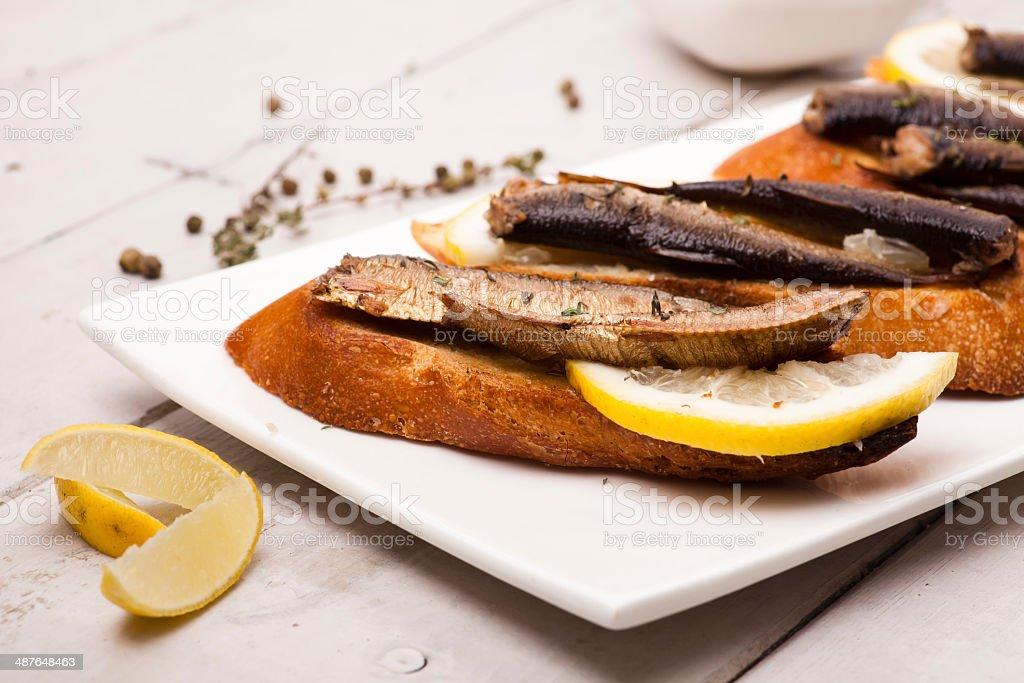 Fish, Spanish tapas - sprat with lemon on baked bread stock photo