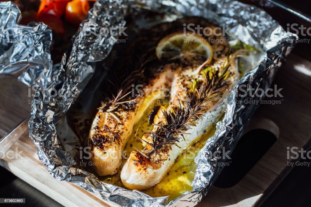 fish steak baked with lemon and herbs in foil stock photo