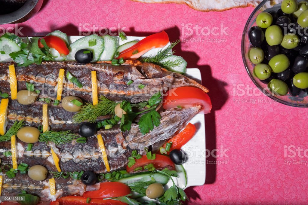 fish sterlet baked sturgeon with fresh vegetables stock photo