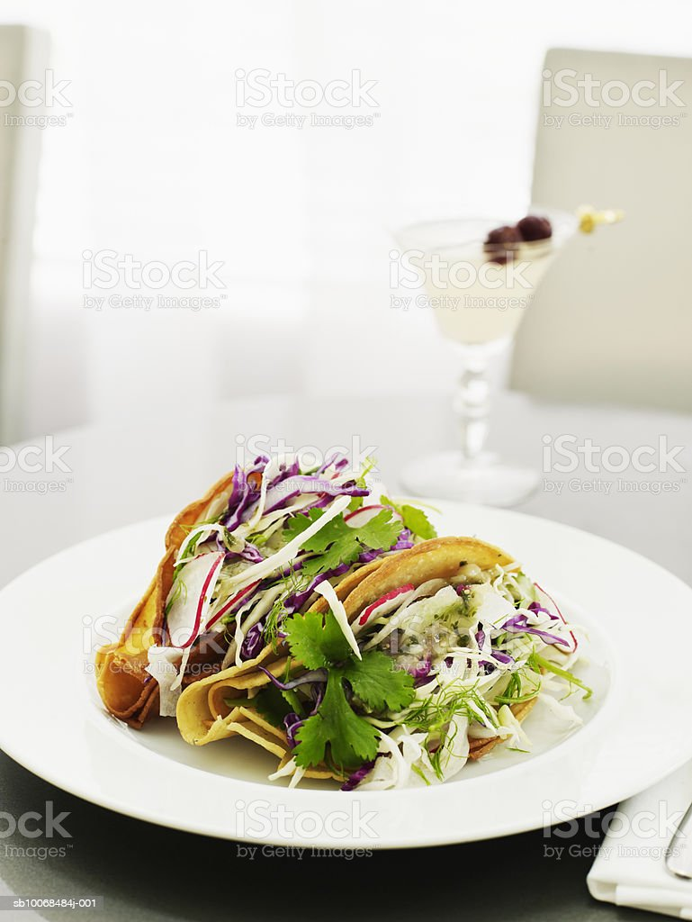 Fish tacos with cod, salsa verde, fennel and cabbage, cocktail in background royalty free stockfoto