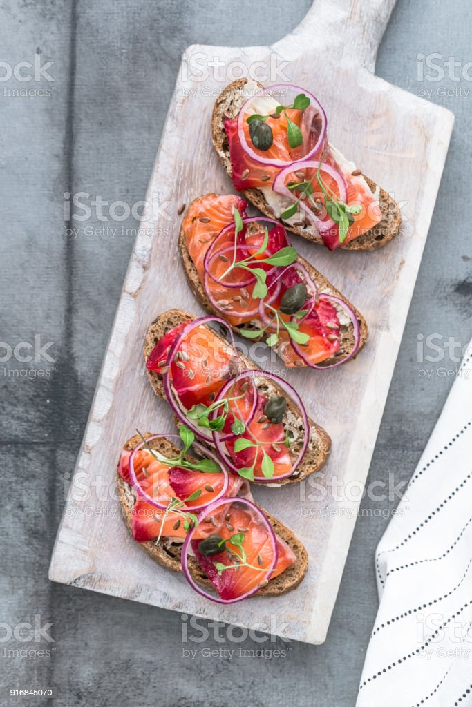 Fish Tapas on Crusty Bread, bread and cured salmon stock photo