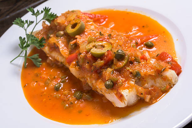 Fish Veracruzana filet of fish cooked Veracruzana style with onions, capers, tomatoes, and olives veracruz stock pictures, royalty-free photos & images