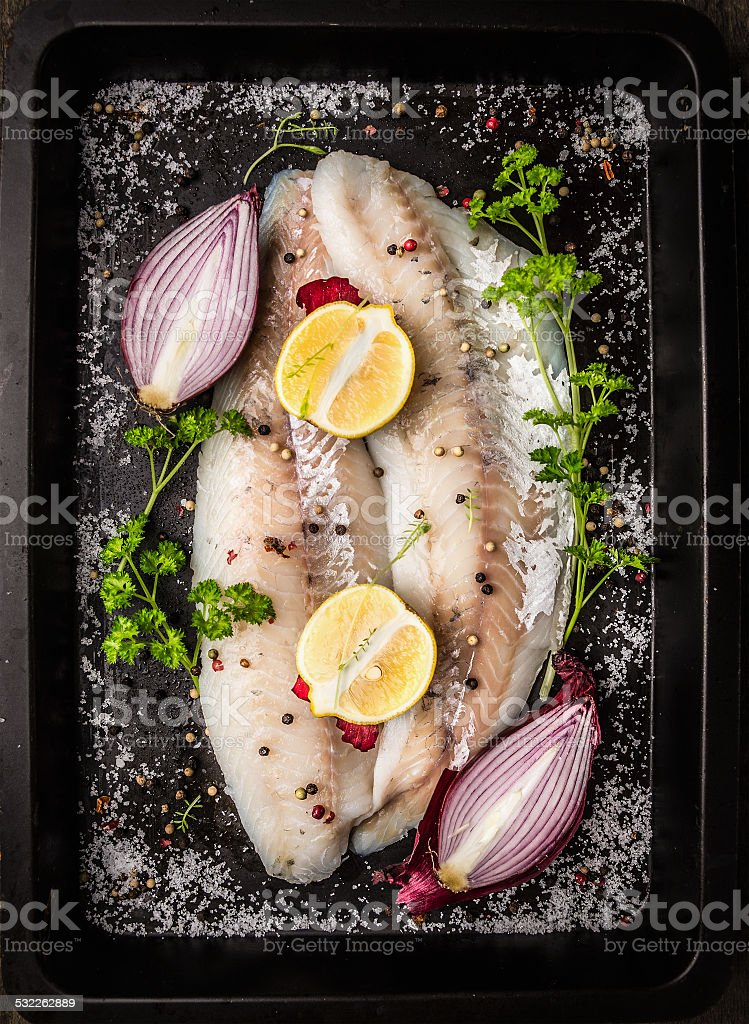 fish with spices,herb,onion,lemon  on backing tray stock photo