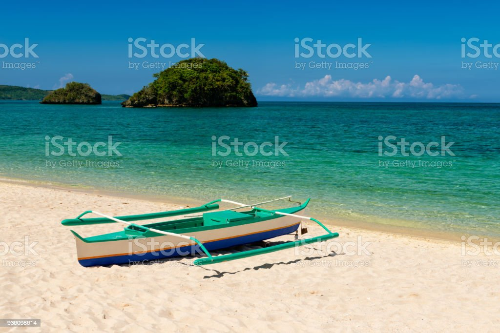 fishboat on sand and two small islands on tropic turquoise sea and blue sky. stock photo
