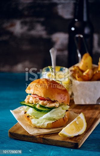 Fishburger with toppings and fries. Rustic style.