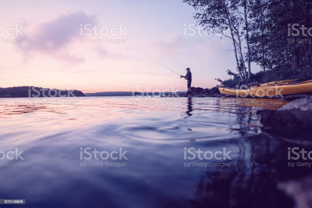 Fisher at a beautiful lake at low light stock photo