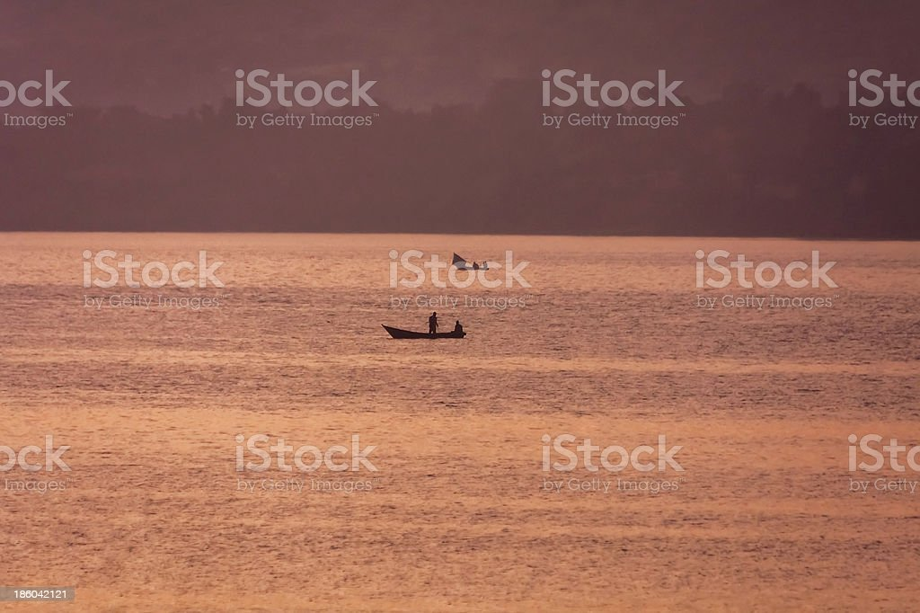 Fisher boats in lake at dawn against hazy bank background stock photo