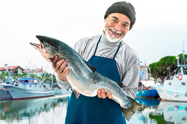 Fisher holding a big atlantic salmon fish Fisher holding a big atlantic salmon fish in the fishing harbor  fisherman stock pictures, royalty-free photos & images
