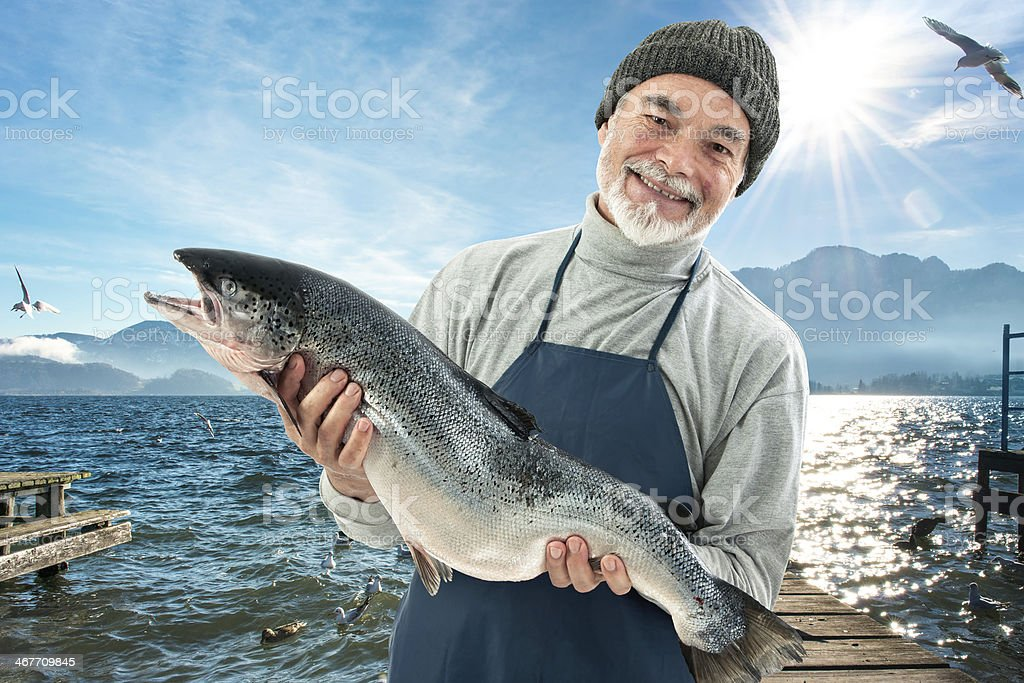 Fisher holding a big atlantic salmon fish stock photo