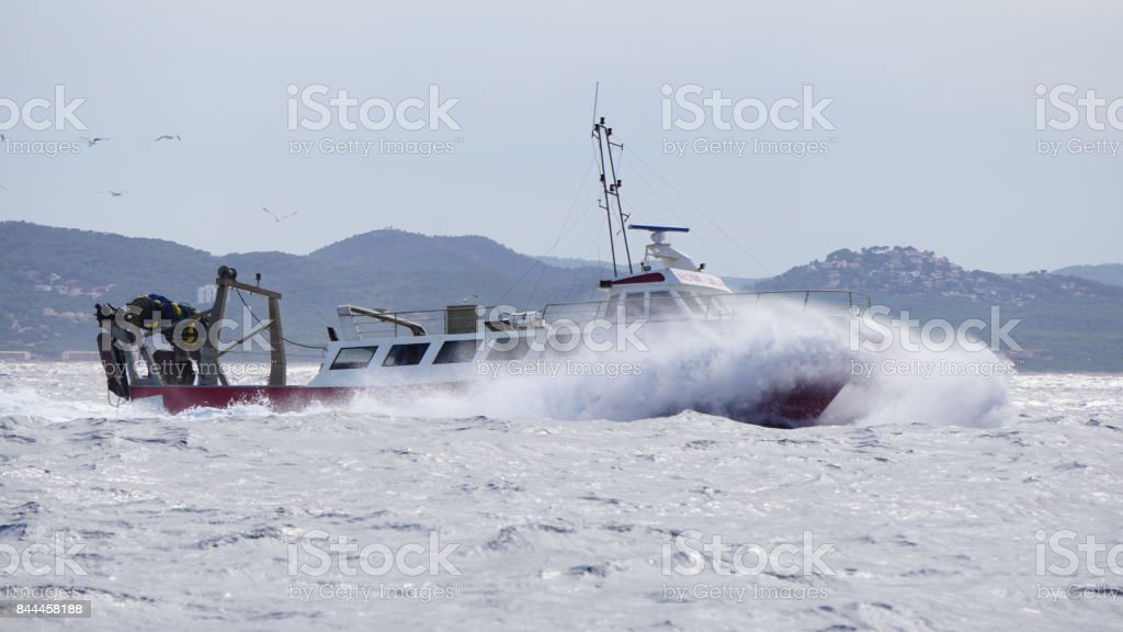 Fisherboat on rough sea with birds stock photo