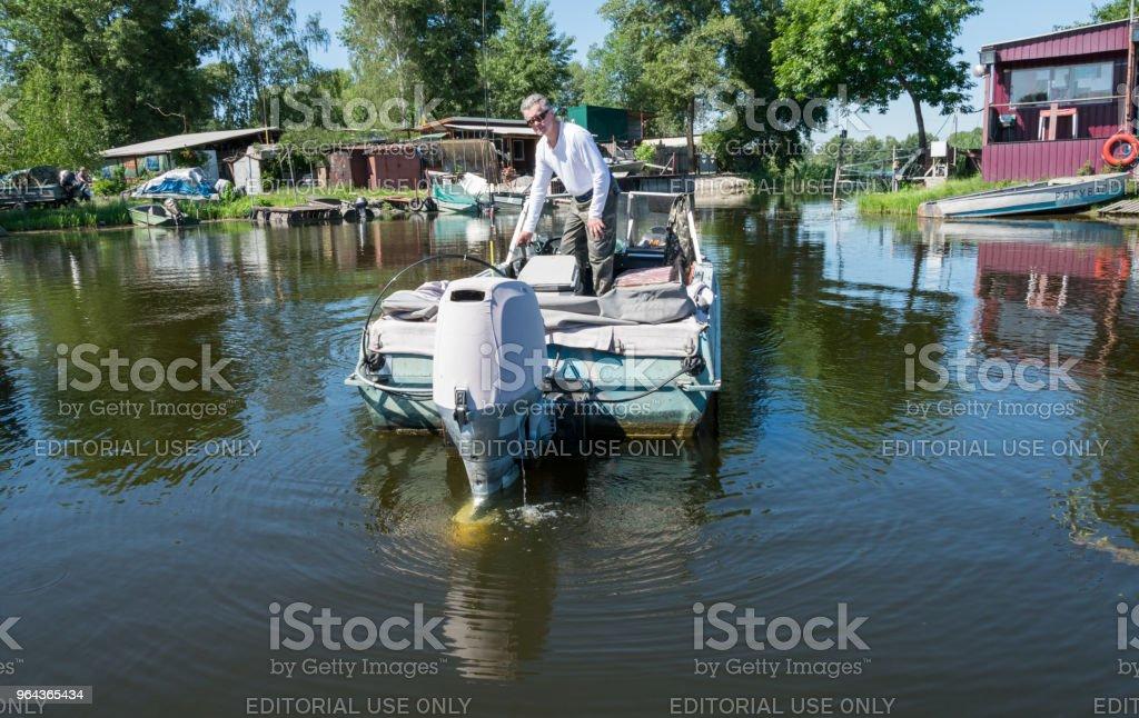 Pescador e um velho barco de pesca. Barcos nas margens do rio Dnieper - Foto de stock de Aldeia royalty-free