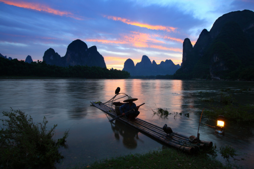 Early morning sunrise with moon and star over karst mountain and villages with a reflection of moonlight on the li river, Yangshuo China