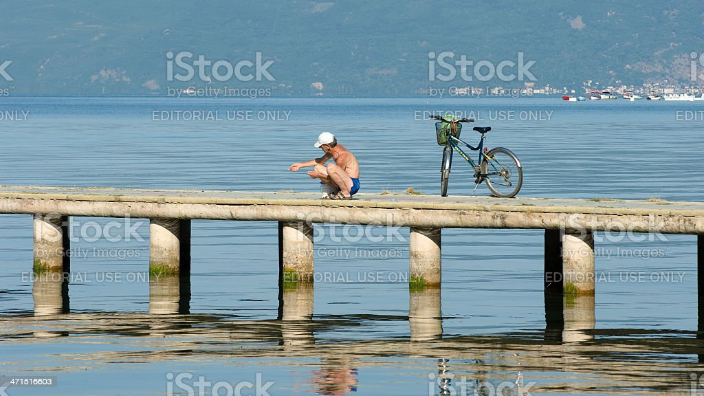 Fisherman And His Bicycle On Jetty Of Ohrid Town royalty-free stock photo