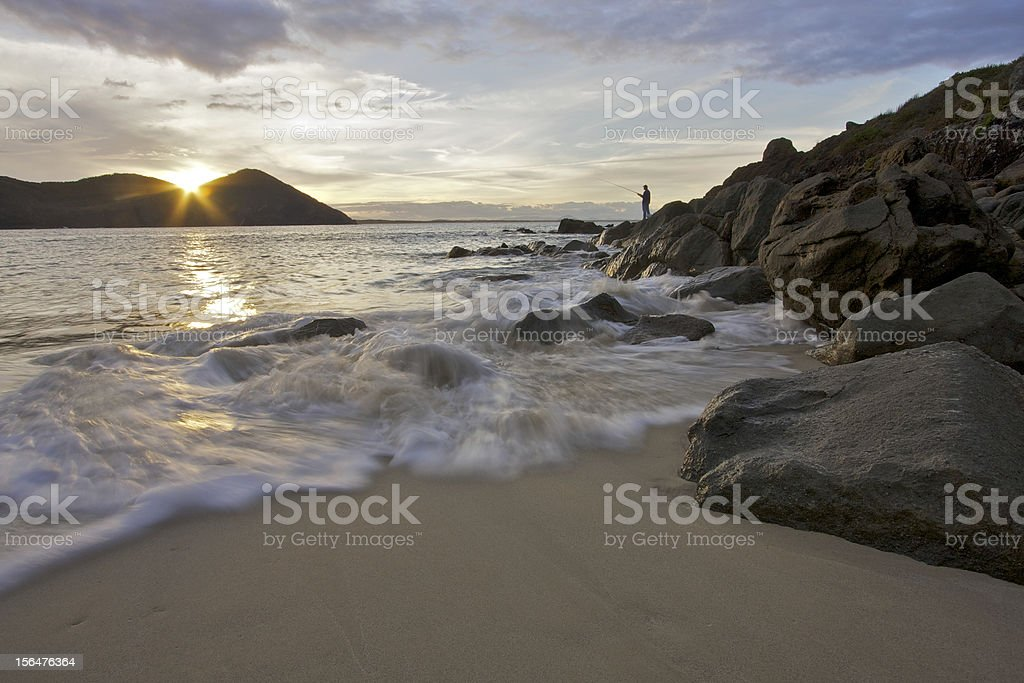 Fisherman at sunset on Shelly Beach royalty-free stock photo
