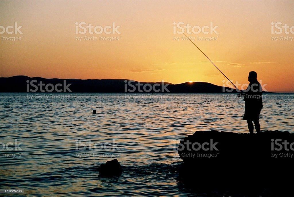 Fisherman at sunset royalty-free stock photo