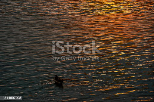 Two (not recognizeable) fishermen in a dug-out canoe at the last daylight. Lake Albert, Uganda.