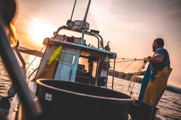 fischer bei der arbeit - segelhandschuhe stock-fotos und bilder