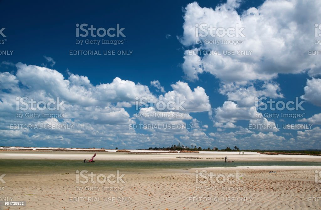 A Fisherman boating back through a lagoon of Indian Ocean in Tanzania under a dramatically clouded sky. stock photo