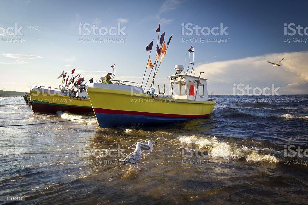 Fisherman boats on the beach in sunset stock photo