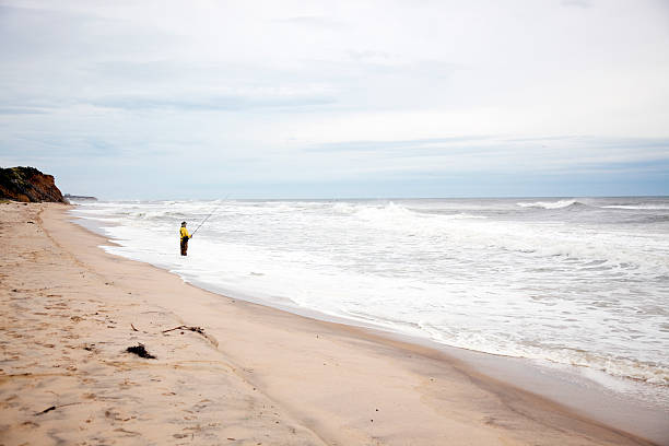 Fisherman by the ocean stock photo