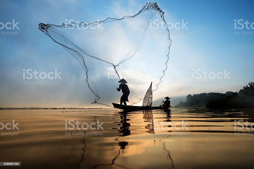 Fisherman casting his net at the sunset. stock photo