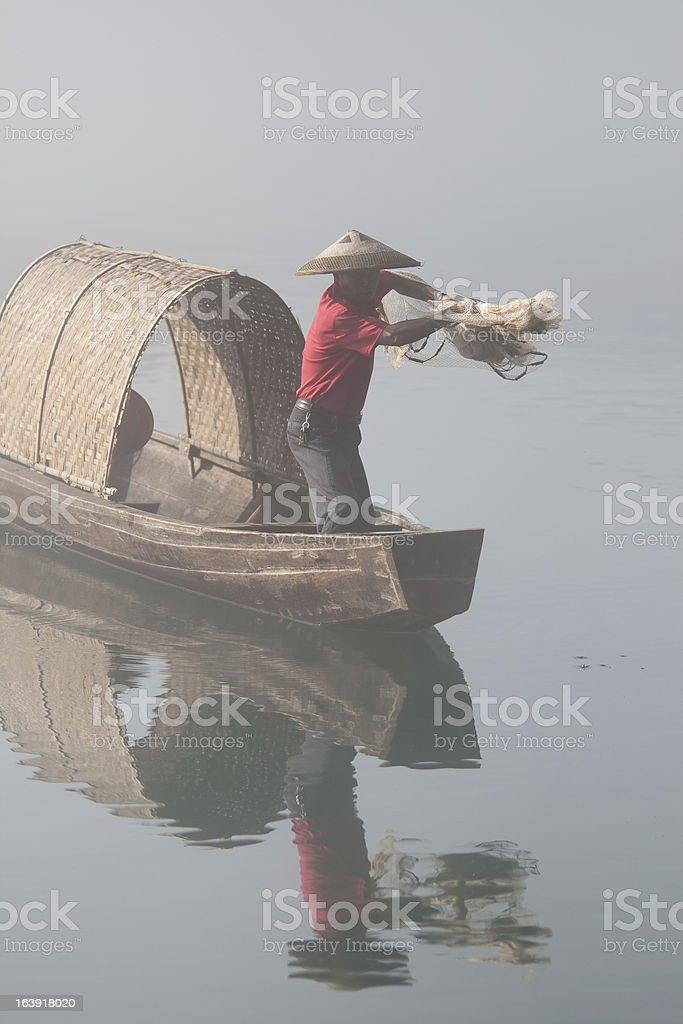 Fisherman casting net on river royalty-free stock photo