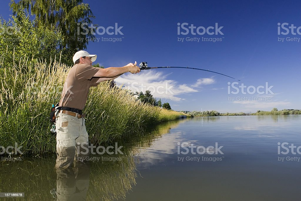 Fisherman Casting on Calm River royalty-free stock photo